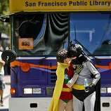 Huckleberry Greenlee, left, kisses Jennifer Collins dressed as cartoon characters Robin and Batman as they march with the San Francisco Public Library in the 40th annual Gay Pride Parade on Sunday in San Francisco.