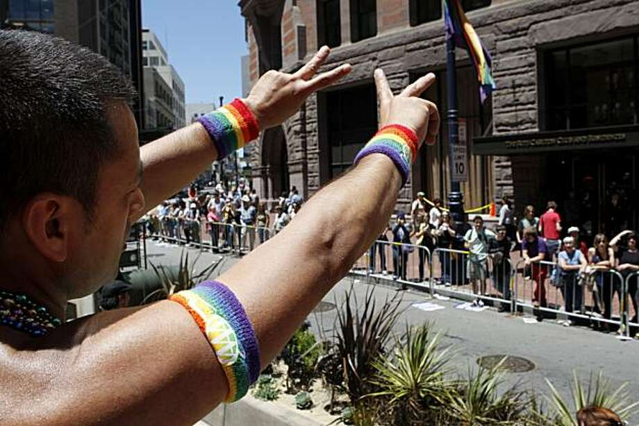 Miguel Rueda flashes the peace sign to spectators at the 40th annual Pride Parade on Sunday in San Francisco. Photo: John Sebastian Russo, The Chronicle