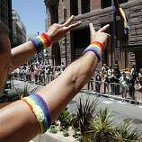 Miguel Rueda flashes the peace sign to spectators at the 40th annual Pride Parade on Sunday in San Francisco.