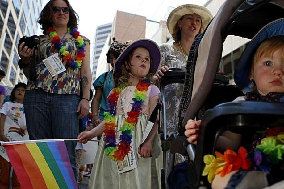 Kate and Kory Sheppard (left to right) wait with their two daughters, 4-year-old Keaton (middle) and 2-year-old Korbyn, to join the 40th annual Pride Parade on Sunday in San Francisco. Photo: John Sebastian Russo, The Chronicle