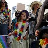 Kate and Kory Sheppard (left to right) wait with their two daughters, 4-year-old Keaton (middle) and 2-year-old Korbyn, to join the 40th annual Pride Parade on Sunday in San Francisco.