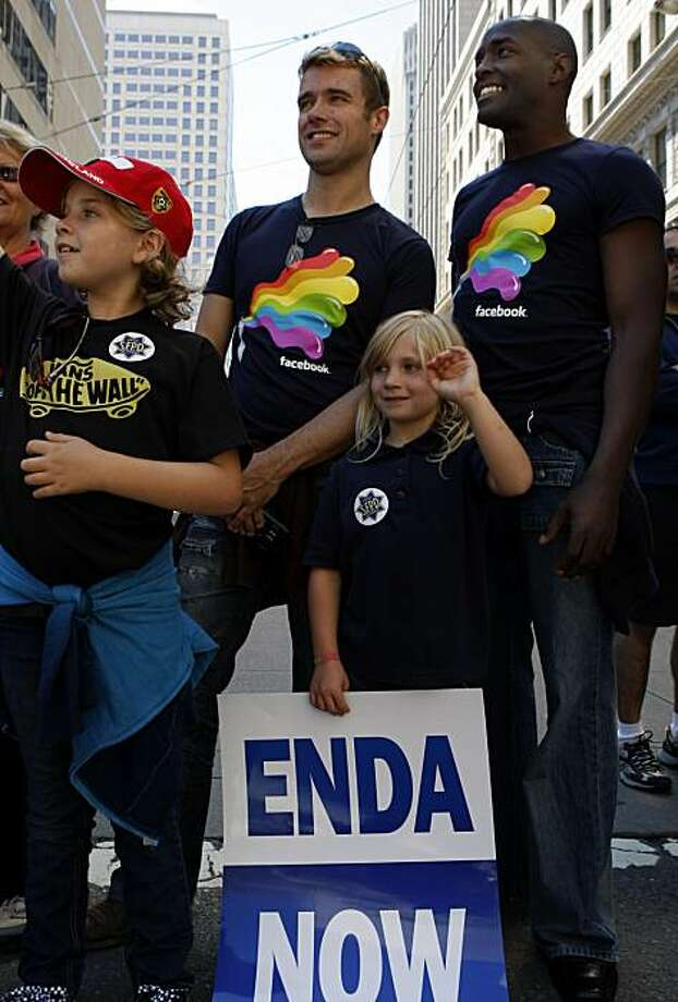 Partners Stu Crabb (left) and Brian Brooks watch the 40th annual Pride Parade pass by on Market Street with Crabb's children, Phoebe, 9, (left) and Esther, 7, on Sunday in San Francisco. Photo: John Sebastian Russo, The Chronicle