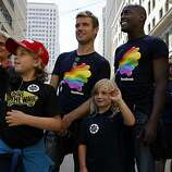 Partners Stu Crabb (left) and Brian Brooks watch the 40th annual Pride Parade pass by on Market Street with Crabb's children, Phoebe, 9, (left) and Esther, 7, on Sunday in San Francisco.