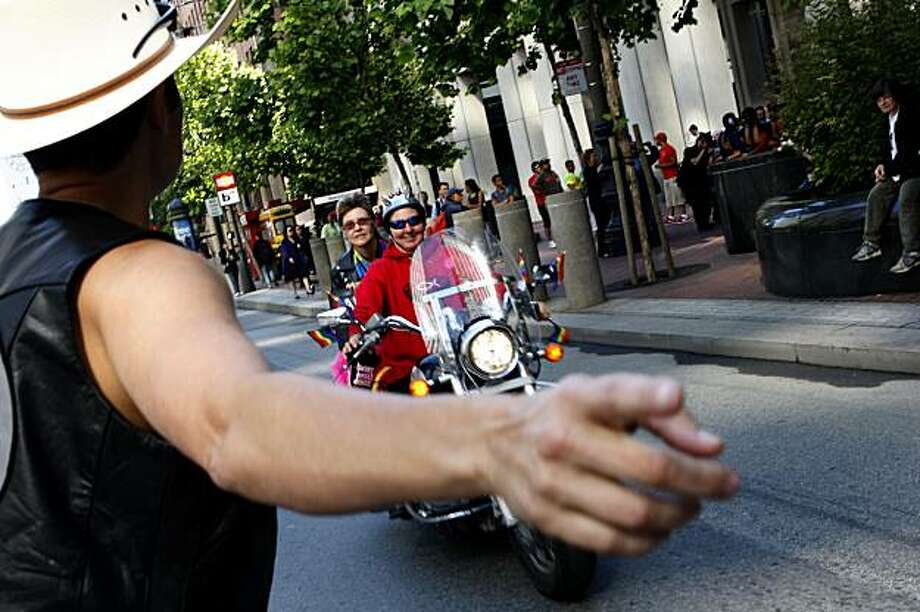 Christine Svendsen of the Monterey Chapter of the Dykes on Bikes directs newly arriving participants of the 40th annual Pride Parade to their rallying points on Market Street on Sunday in San Francisco. Photo: John Sebastian Russo, The Chronicle