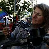 Gail Tillotson of Santa Rosa checks her hair in the mirror of her motorcycle shortly before the Dykes on Bikes lead the way down Market Street during the 40th annual Pride Parade on Sunday in San Francisco.