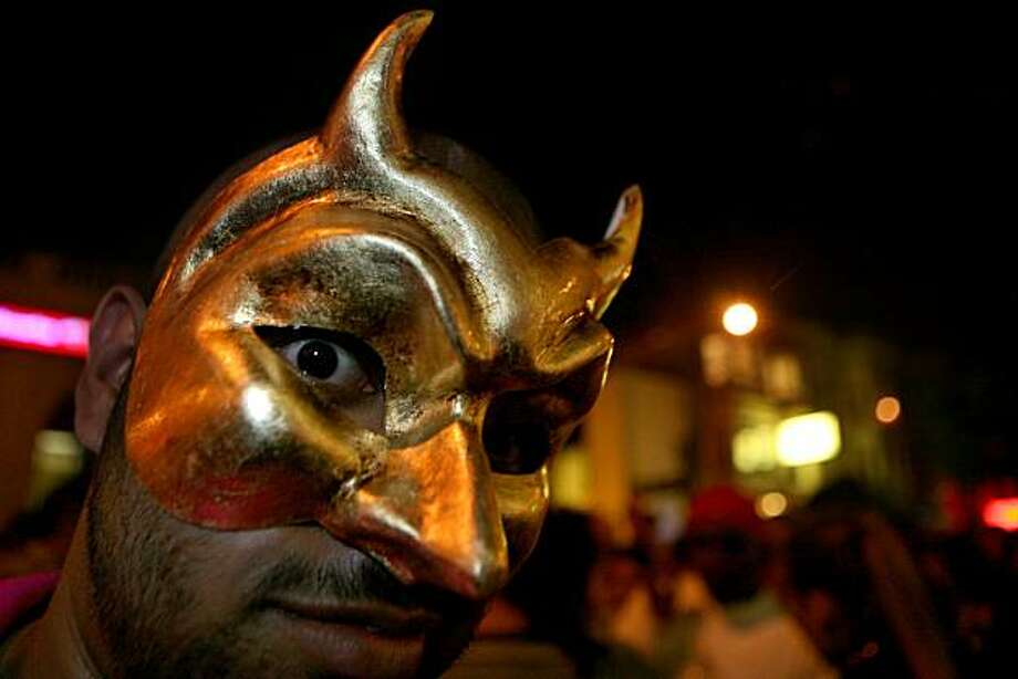 Eriq Martin of San Francisco wore a mask he purchased at the North Beach Festival to join the celebration in the Castro District after the 18th Annual San Francisco Dyke March from Dolores Park to the Castro. Photo: Kat Wade, Special To The Chronicle