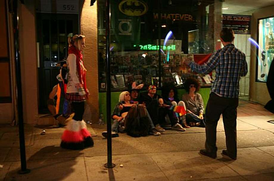 Lizzy Heald, left, watches Daniel Metzger entertain party-goers with twirling glow sticks at the after party early Sunday for Saturday's 18th Annual San Francisco Dyke March from Dolores Park to the Castro. Photo: Kat Wade, Special To The Chronicle