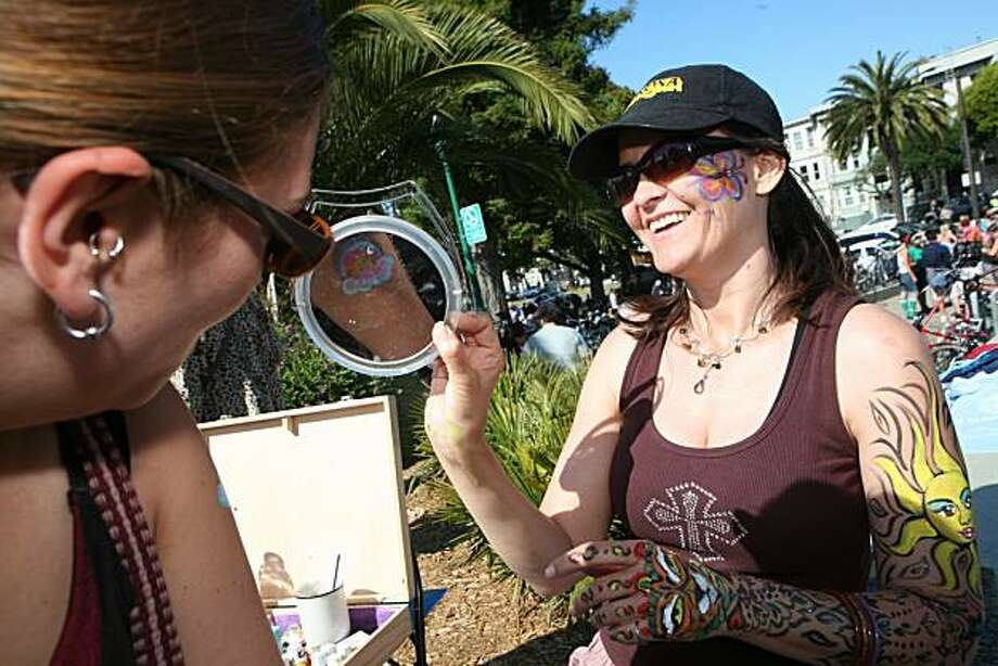 Abbey Buckley of Ann Arbor, Mich., gets a looks at the rainbow painted on her arm by Tammy Artis of Berkeley at the 18th annual Dyke March celebration in Dolores Park in San Francisco on Saturday. Photo: Kat Wade, Special To The Chronicle