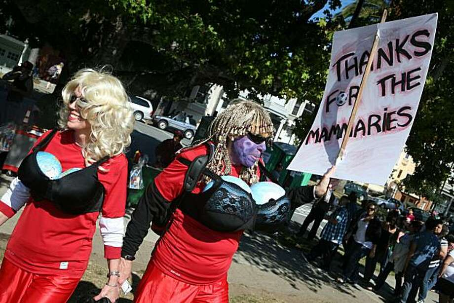 "Susan Kennedy, left, and Marny Hall of Oakland, carry a sign reading ""thanks for the mammaries"" during the 18th annual Dyke March celebration in Dolores Park in San Francisco on Saturday. Photo: Kat Wade, Special To The Chronicle"