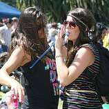 Jessica Thompson, left, gives her friend Jill Kauble of Chico a drink of wine from her backpack while they dance at the 18th annual Dyke March celebration in Dolores Park in San Francisco on Saturday.