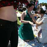 "Marika Cifor of Oakland exposes her belly while Margaret Hasley of San Francisco gets help putting on sunscreen from ""nurse"" Sarai Coutin of Santa Monica at the 18th annual Dyke March celebration in Dolores Park in San Francisco on Saturday."