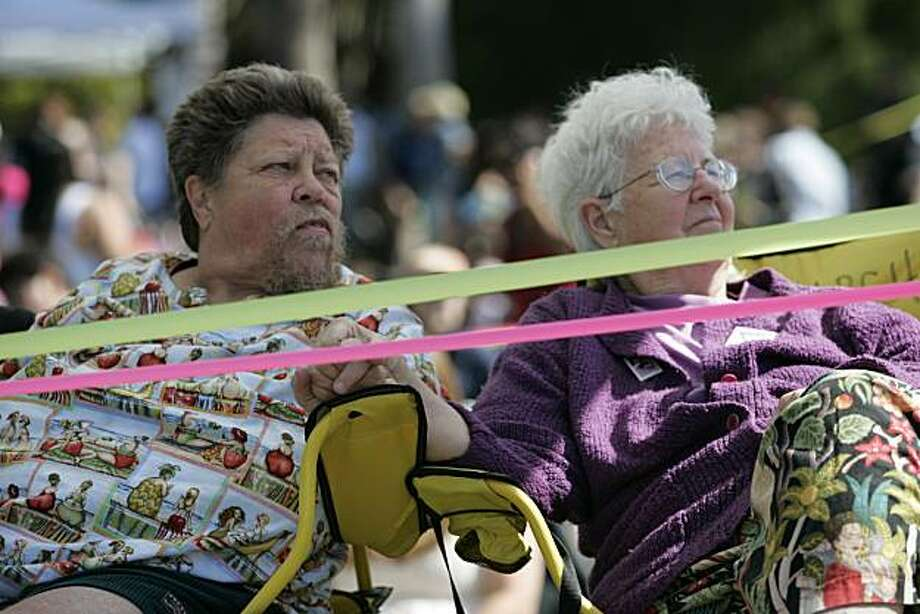 "Ardy Tibby, left, sits in the disabled section with her partner of more than nine years, Jean Taylor, at the 18th annual Dyke March celebration in Dolores Park in San Francisco on Saturday. Tibby and Taylor traveled from Melbourne, Australia, to join marches in L.A. and San Francisco before heading to Ohio for a gathering of ""Old Lesbians."" Photo: Kat Wade, Special To The Chronicle"