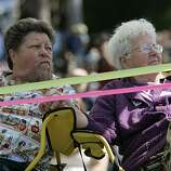 "Ardy Tibby, left, sits in the disabled section with her partner of more than nine years, Jean Taylor, at the 18th annual Dyke March celebration in Dolores Park in San Francisco on Saturday. Tibby and Taylor traveled from Melbourne, Australia, to join marches in L.A. and San Francisco before heading to Ohio for a gathering of ""Old Lesbians."""