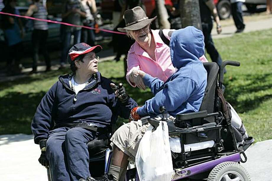 Patty Overland, left, and Monique Davis are greeted at the 18th annual Dyke March celebration in Dolores Park in San Francisco on Saturday. Photo: Kat Wade, Special To The Chronicle