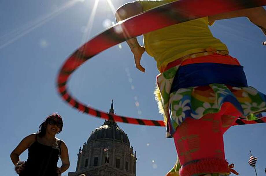 Alyssa Currie of Sacramento Hula-Hoops while friend Kittie Lynne watches during the Pride kick-off party at Civic Center Plaza on Saturday in San Francisco. Photo: John Sebastian Russo, The Chronicle
