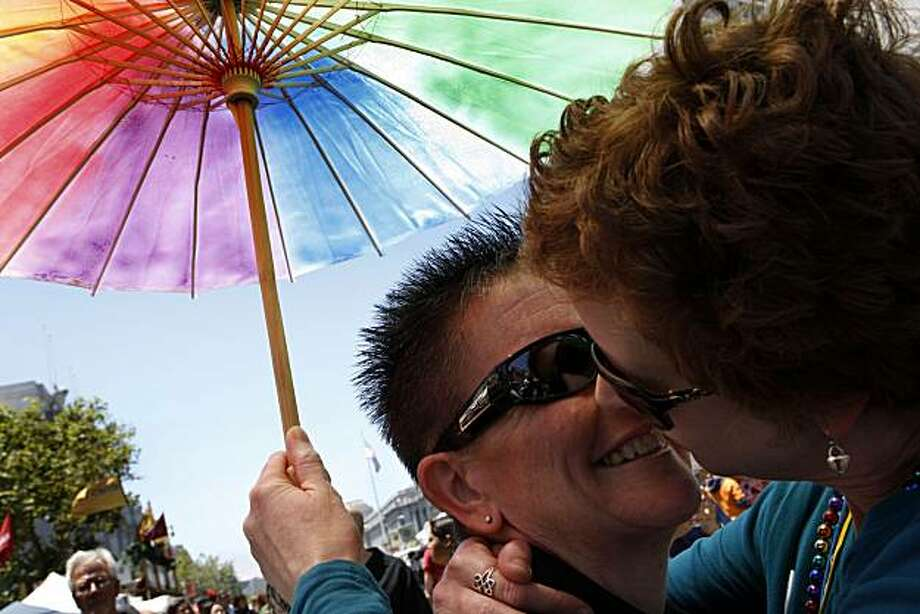 Rasha Wyndsong (left) kisses her partner, Leslie Neely, both of San Luis Obispo, at the Pride kick-off party at Civic Center Plaza on Saturday in San Francisco. Photo: John Sebastian Russo, The Chronicle