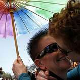 Rasha Wyndsong (left) kisses her partner, Leslie Neely, both of San Luis Obispo, at the Pride kick-off party at Civic Center Plaza on Saturday in San Francisco.