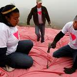 (left to right) Kimiko Barbour Stephan Handorf and Ron Podoske finish securing pink tarps to the hillside during the annual Pink Triangle installation on Christmas Tree Road in Twin Peaks on Saturday, June 26, 2010 in San Francisco, Calif.