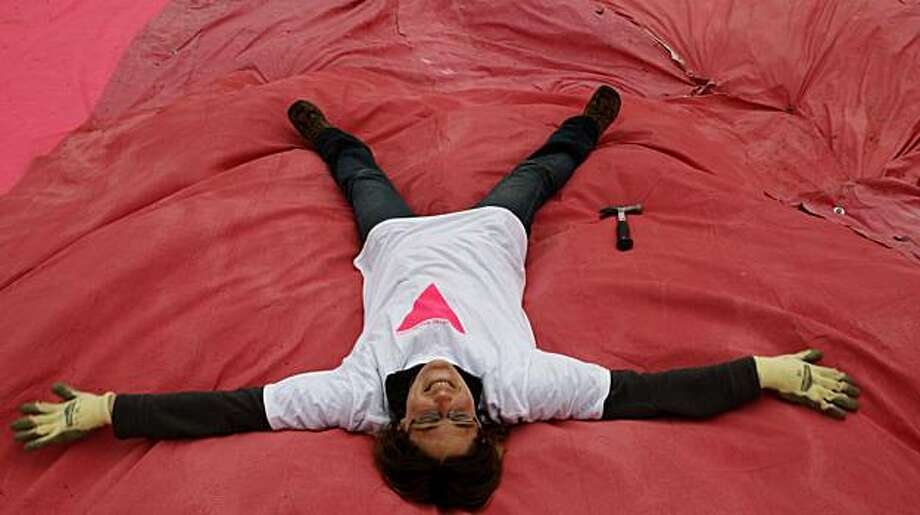 Volunteer Sasha Harris-Cronin has fun flattening the brush and bushes underneath the pink triangle during its annual installation on a hillside  in Twin Peaks on Saturday, June 26, 2010 in San Francisco, Calif. Photo: John Sebastian Russo, The Chronicle