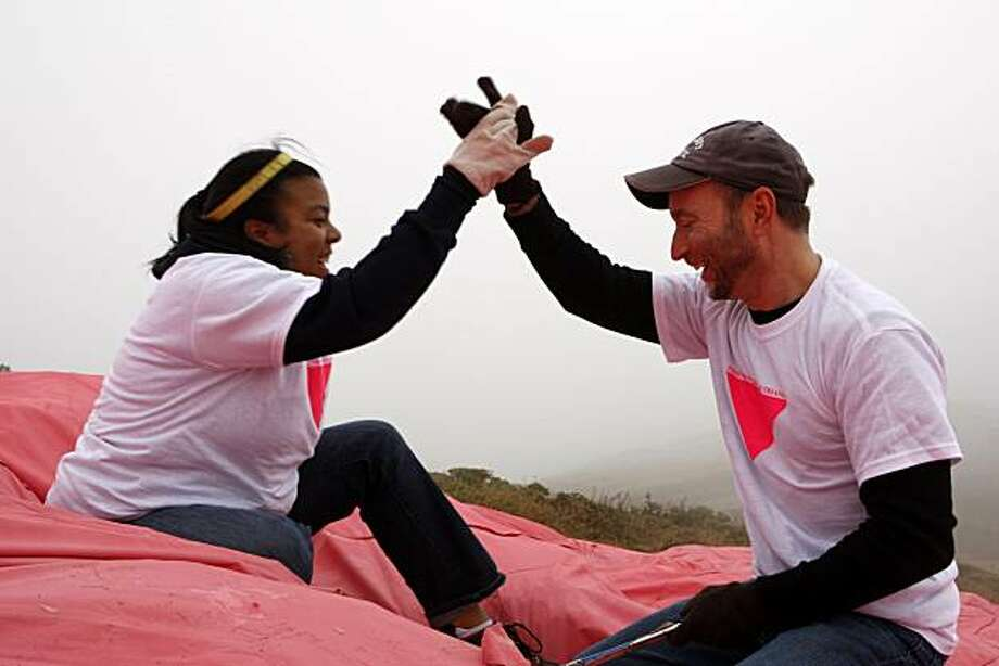 Volunteers Kimiko Barbour (left) high-fives Ron Podoske for their efforts during the annual installation of the Pink Triangle installation on Christmas Tree Road in Twin Peaks on Saturday, June 26, 2010 in San Francisco, Calif. Photo: John Sebastian Russo, The Chronicle