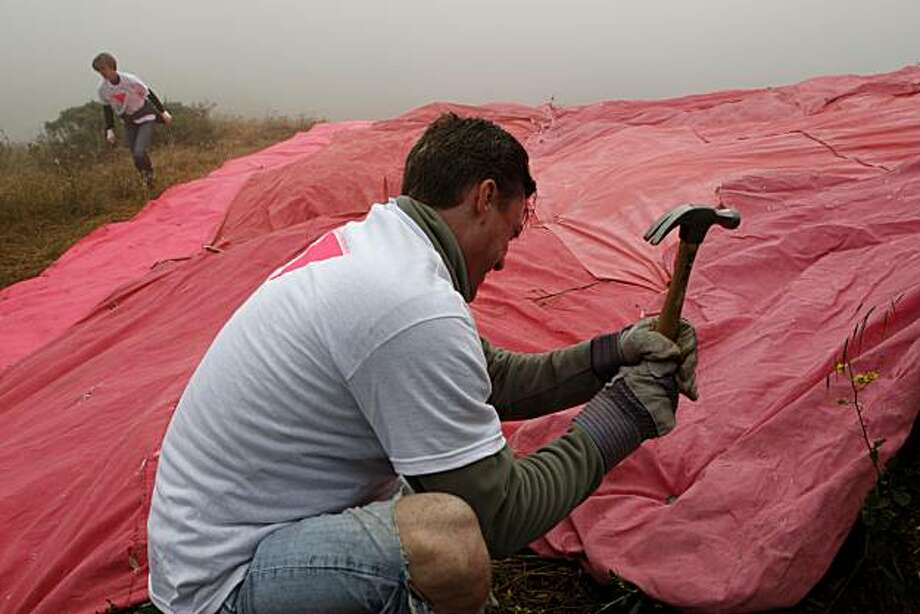 Volunteer Craig Thompson of San Francisco drives a stake into the Twin Peaks hillside during the annual installation of the Pink Triangle on Christmas Tree Road on Saturday, June 26, 2010 in San Francisco, Calif. Photo: John Sebastian Russo, The Chronicle