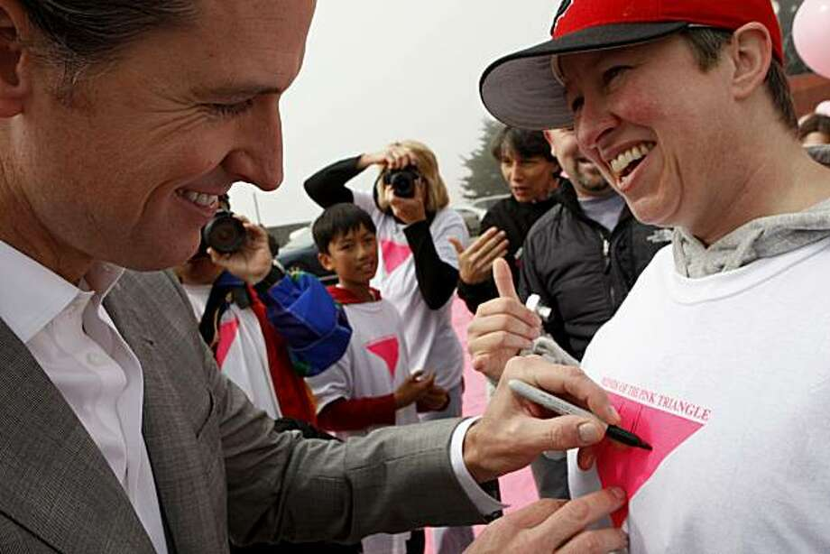 Mayor Newsom signs the shirt of volunteer Jennifer Lyson during a brief appearance at the Pink Triangle installation on Christmas Tree Road in Twin Peaks on Saturday, June 26, 2010 in San Francisco, Calif. Photo: John Sebastian Russo, The Chronicle