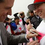 Mayor Newsom signs the shirt of volunteer Jennifer Lyson during a brief appearance at the Pink Triangle installation on Christmas Tree Road in Twin Peaks on Saturday, June 26, 2010 in San Francisco, Calif.