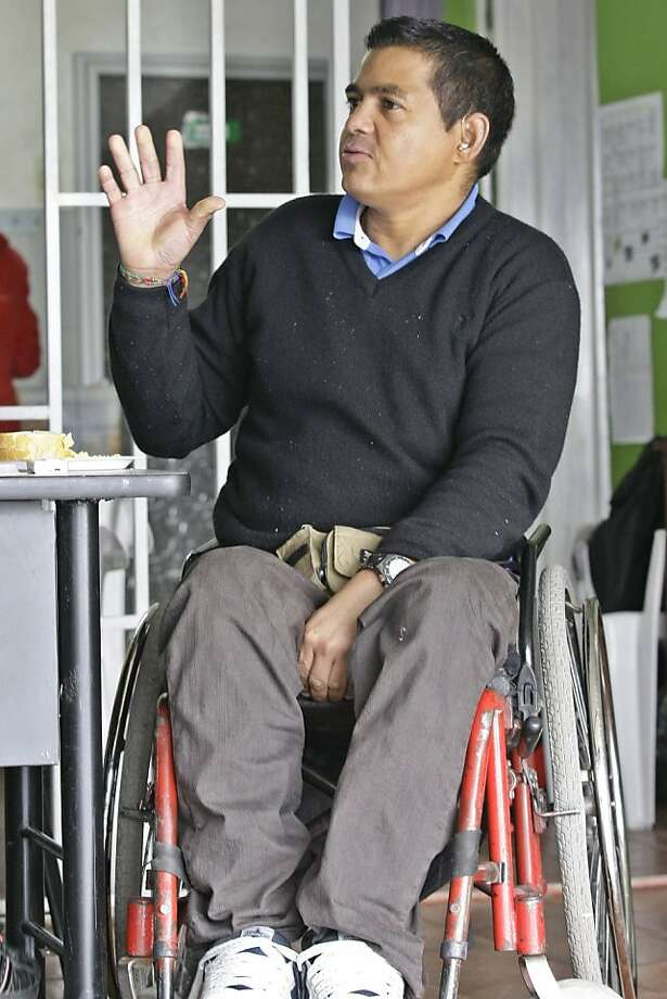 In this Oct. 28, 2011 photo, Sabas Duque, a former rebel from the Revolutionary Armed Forces of Colombia (FARC), speaks during an interview in Bogota, Colombia. Duque, who uses a wheelchair because he was partially paralyzed in a shooting, now helps run a Bogota workshop that teaches craft-making with papier-mâché and fabric. But he knows plenty of other ex-fighters who have left their jobs and drifted back to gunslinging. Thousands of former combatants in Colombia's long-running conflict who surrendered their weapons to the government have since discovered the downside to civilian life: unemployment. From both sides of the old battle lines, former right-wing militiamen and leftist rebels are being lured into jobs for emerging crime rings - a new security threat that ranks among the biggest challenges confronting President Juan Manuel Santos' government. (AP Photo/Nestor Silva) Photo: Nestor Silva, Associated Press