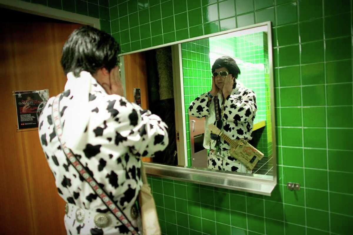 Elvince, aka Vince Hill of Bellingham, attatches his sideburns in the men's restroom during the