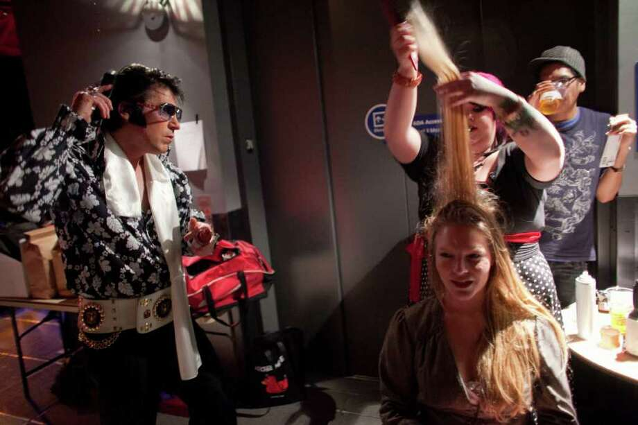 "Elvis, aka Bret Wiggins, left, checks his hair as backup singer Shandell Warren has her hair styled backstage during the ""Seattle Invitationals"" Elvis Tribute Artist competition at the EMP. To commemorate the 50th anniversary of the Seattle World's Fair, Elvis returned to the Seattle Center for the 15th annual event on Saturday, January 14, 2012. Photo: JOSHUA TRUJILLO / SEATTLEPI.COM"