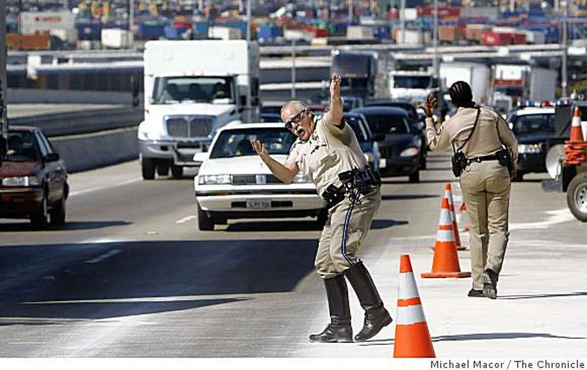 CHP officer Rob Barrera directs drivers to speed up and move along near a big rig crash site in Oakland.