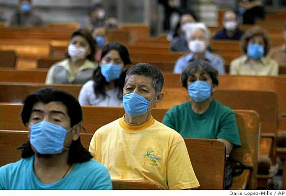 Faithful wearing face masks, who managed to get inside a closed door mass, listen at the Metropolitan cathedral in Mexico City, Sunday, April 26, 2009. Churches stood empty Sunday in Mexico City after services were canceled, and health workers screened airports and bus stations for people sickened by a new strain of swine flu that experts fear could become a global epidemic. (AP Photo/Dario Lopez-Mills) Photo: Dario Lopez-Mills, AP
