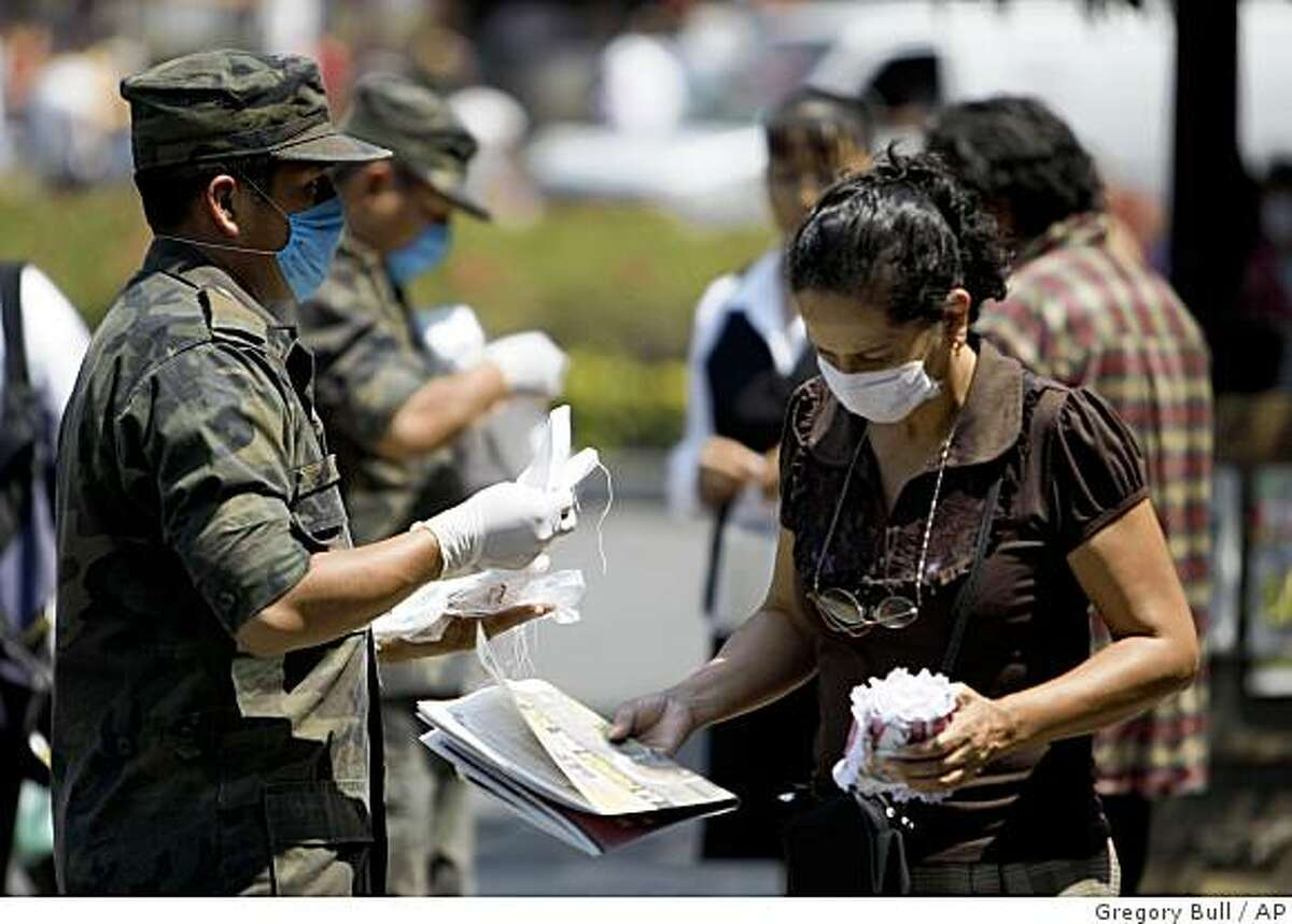 Soldiers pass out surgical masks in Mexico City, Saturday, April 25, 2009. Mexico City canceled hundreds of public concerts, sporting events and meetings on Saturday as authorities in this overcrowded capital tried to contain an outbreak of a deadly new form of swine flu that world health officials warn could become a pandemic. (AP Photo/Gregory Bull)
