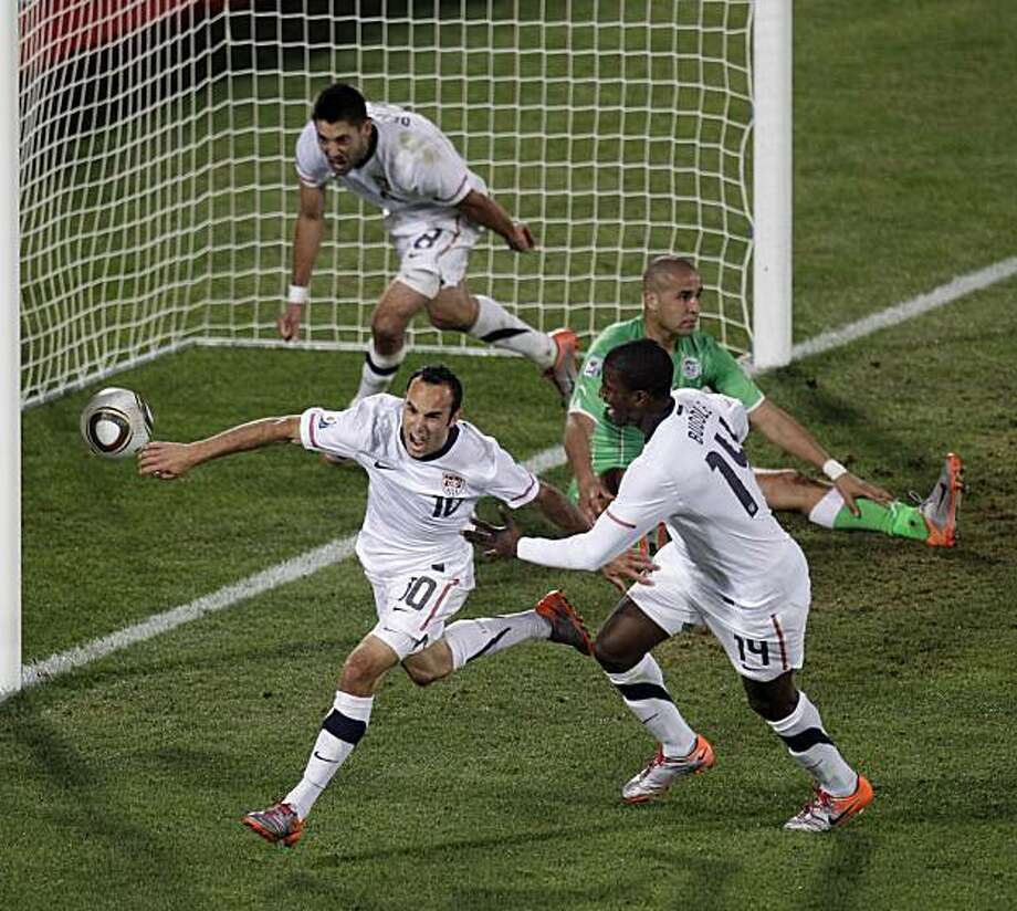 United States' Landon Donovan, front left, celebrates after scoring a goal with fellow team members United States' Clint Dempsey, back left, and United States' Edson Buddle, front right, during the World Cup group C soccer match between the United Statesand Algeria at the Loftus Versfeld Stadium in Pretoria, South Africa, Wednesday, June 23, 2010. Photo: Michael Sohn, AP