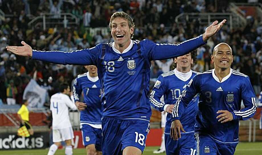 Argentina's Martin Palermo celebrates scoring his side's second goal with Argentina's Clemente Rodriguez, right, and Argentina's Lionel Messi, center, during the World Cup group B soccer match between Greece and Argentina at Peter Mokaba Stadium in Polokwane, South Africa, Tuesday, June 22, 2010. Photo: Eugene Hoshiko, AP