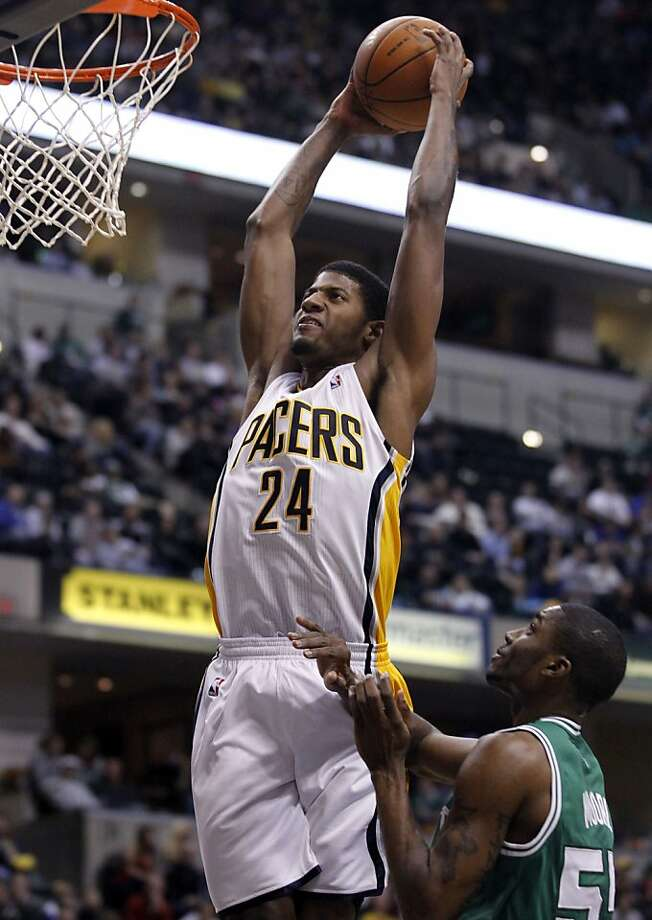 Indiana Pacers guard Paul George, top, goes up over Boston Celtics guard E'Twaun Moore for a dunk in the second half of an NBA basketball game in Indianapolis, Saturday, Jan. 14, 2012. The Pacers defeated the Celtics 97-83. (AP Photo/Michael Conroy) Photo: Michael Conroy, Associated Press
