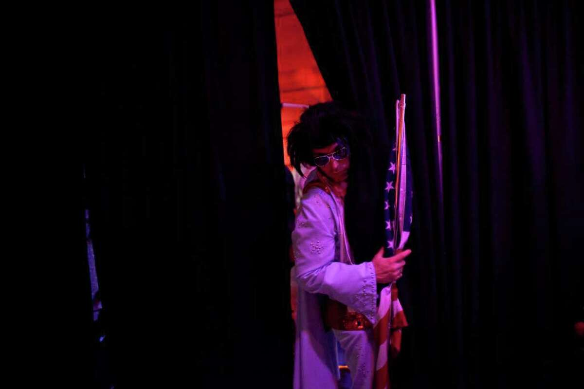 Mike Dippery of Everett, aka Elvis peeks from backstage during the