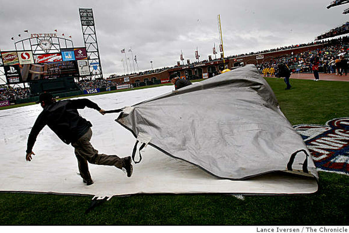 A worker pulls the tarp off the infield to the cheers of the crowd for the Giants opener on Tuesday, April 7, 2009 vs. Milwaukee at AT&T Park.