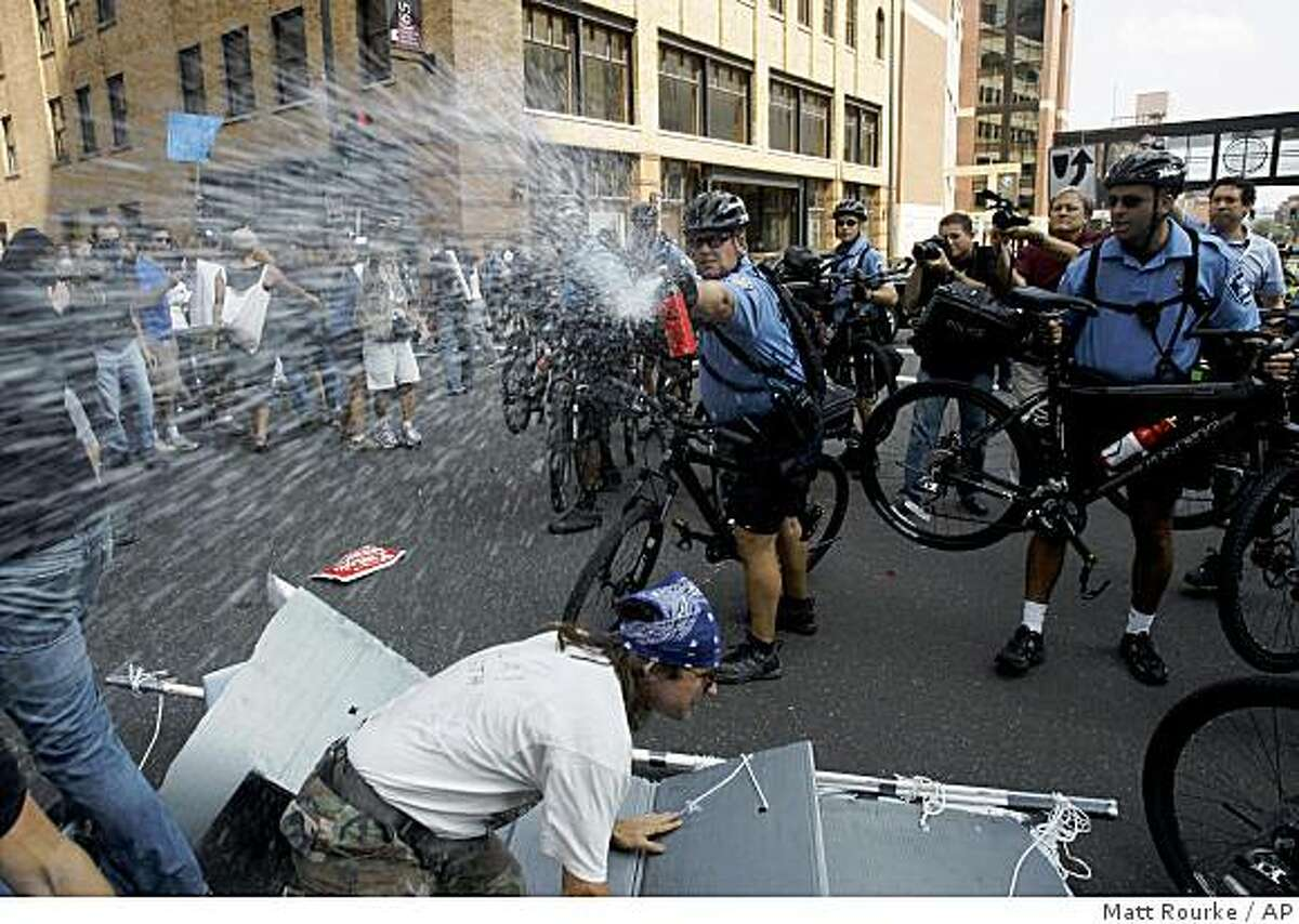 Police officers spray pepper spray at a group of protesters during an anti-war rally at the Republican National Convention in St. Paul, Minn., Monday, Sept. 1, 2008. (AP Photo/Matt Rourke)