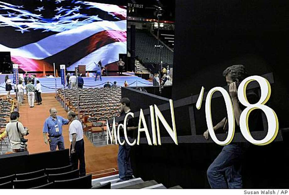 Stagehands carry a sign onto the floor as preparations are underway for the Republican National Convention in St. Paul, Minn. Photo: Susan Walsh, AP