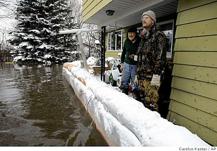 Herb Read, left, and his son Tom Read look out over the flooded Red River as it rises up against  sandbags that protect their home, Wednesday, March 25, 2009 in Hickson, N.D. They refused evacuation from the U.S. Coast Guard. Photo: Carolyn Kaster, AP