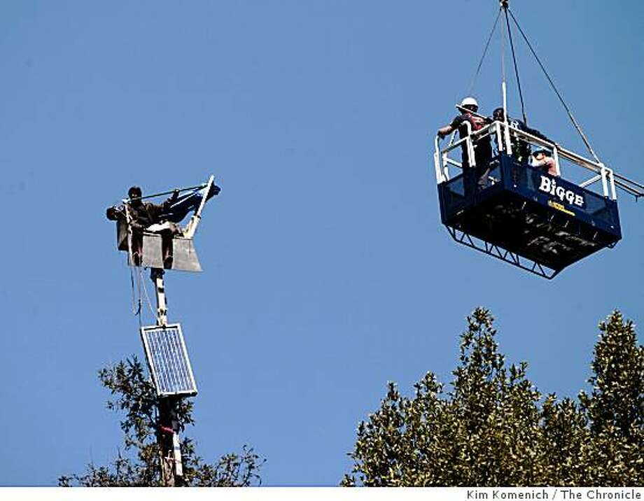 With resistance from the protesters, officials in a basket suspended from a construction crane begin to remove some of the equipment that tree-sitting protesters hauled up a redwood tree west of Memorial Stadium on the  U. C, Berkeley campus in Berkeley, Calif., on Thursday, Aug. 21, 2008. Photo: Kim Komenich, The Chronicle