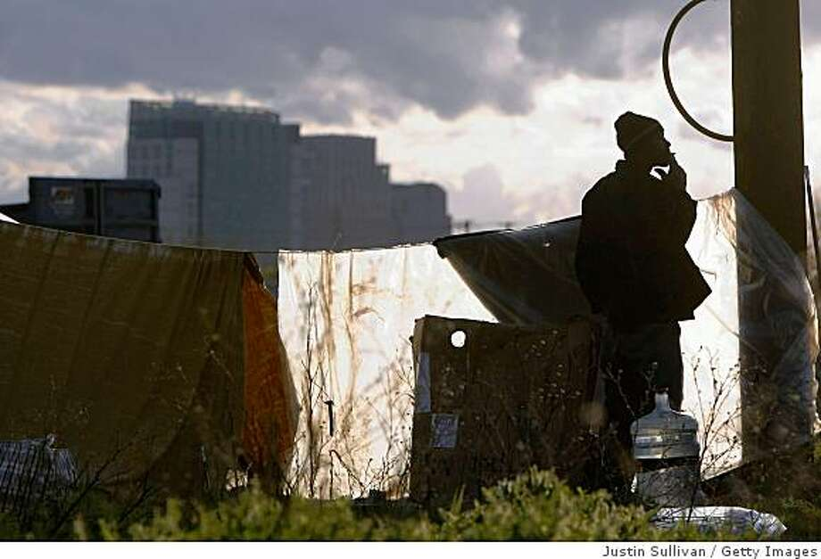 A homeless man smokes a cigarette as he stands in a homeless tent city March 4, 2009 in Sacramento, California. The tent city is seeing an increase in population as the economy worsens and more people are becoming unemployed and having their homes slip into foreclosure. Photo: Justin Sullivan, Getty Images