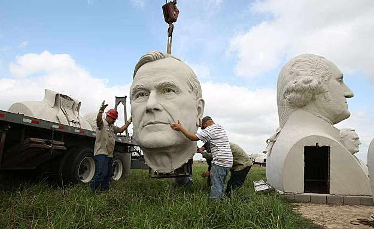 RWS Crane & Rigging employees and local artist David Adickes' assistants disassemble and remove the bust of George H.W. Bush, Tuesday, April 6, 2010, in Pearland, Texas. Six busts of presidents were removed because the land they were placed on is under foreclosure. The development company who owns the statues is return the statues to artist David Adickes.