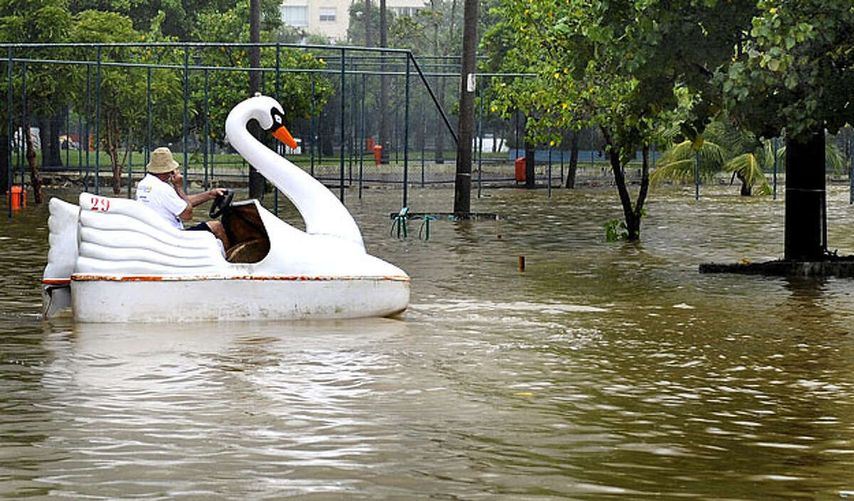 A man pedals a swan paddle boat in a flooded parking lott in front of the Rio de Janeiro's landmark Rodrigo de Freitas lagoon Rio de Janeiro, on April 6, 2010. Flooding from torrential rains and deadly mudslides claimed at least 77 lives in Brazil's Rio de Janeiro state, authorities said Tuesday. Civil defense officials said about half of the fatalities occurred in Rio de Janeiro city, where authorities urged residents to remain indoors and not venture downtown, where streets were impassable.