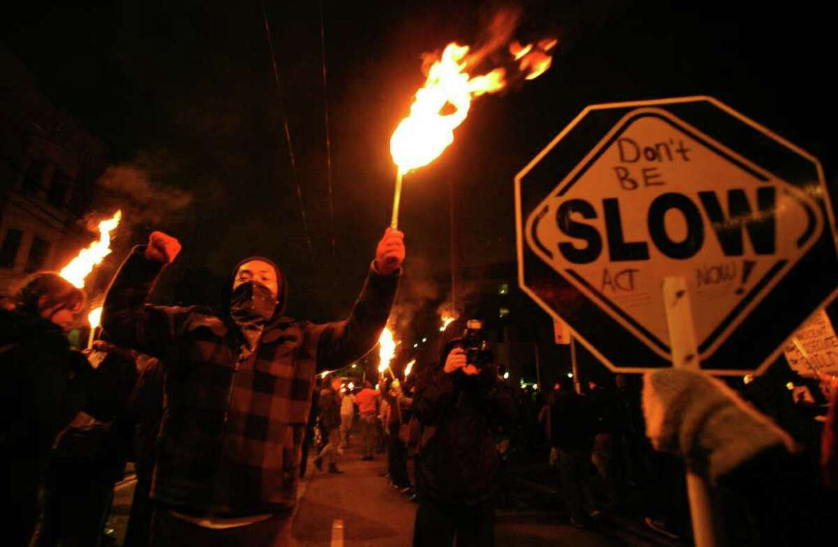 Nearing the Seattle Police Department's East Precinct on 12th Ave, protesters carry lit torches to honor those killed by police on Saturday, Jan. 14, 2012. The protesters, who marched to the Seattle Police Department's East Precinct from 23rd and Union, called for the resignation of Chief John Diaz.