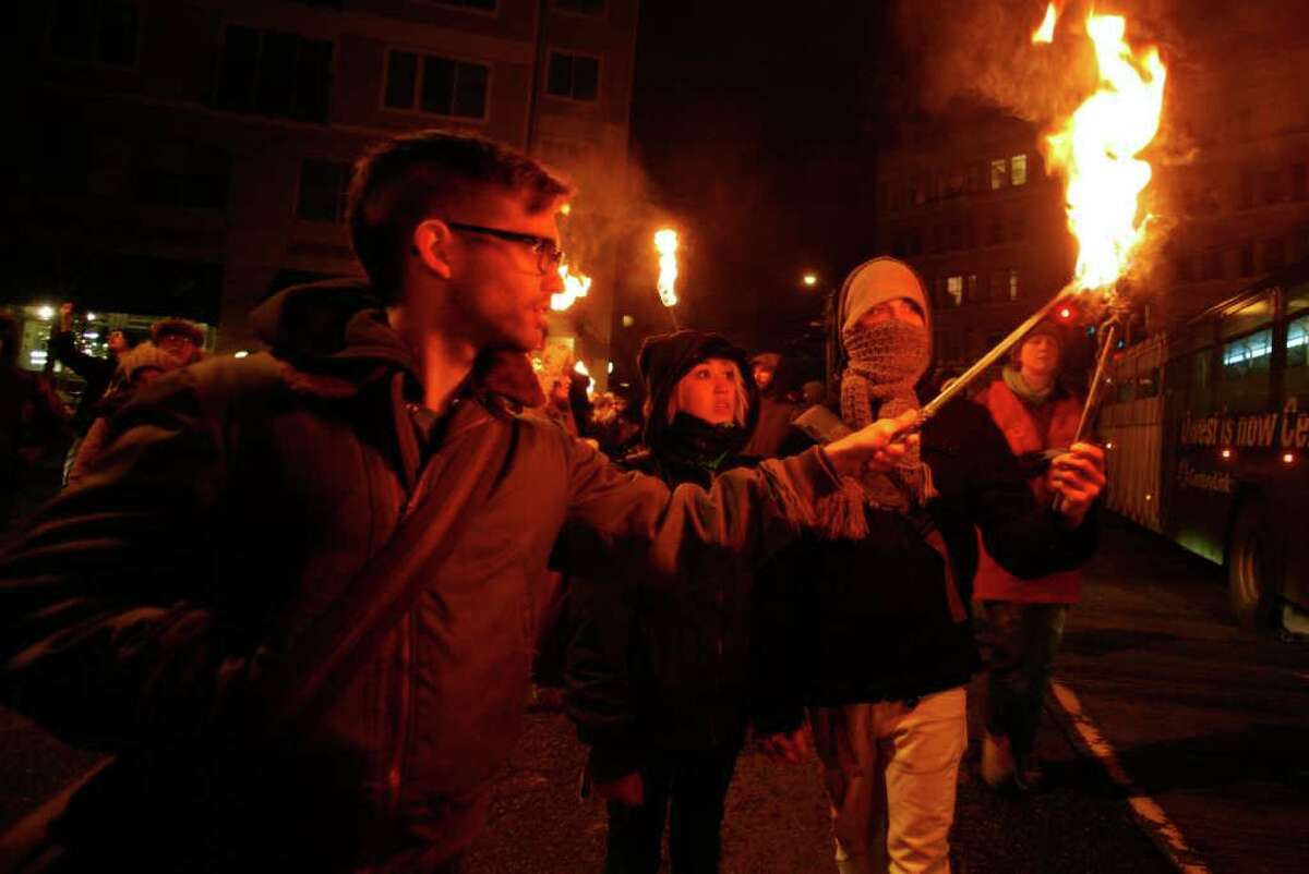 Protesters help keep torches lit as they near the Seattle Police Department's East Precinct on 12th Ave on Saturday, Jan. 14, 2012. The protesters, who marched to the Seattle Police Department's East Precinct from 23rd and Union, called for the resignation of Chief John Diaz.