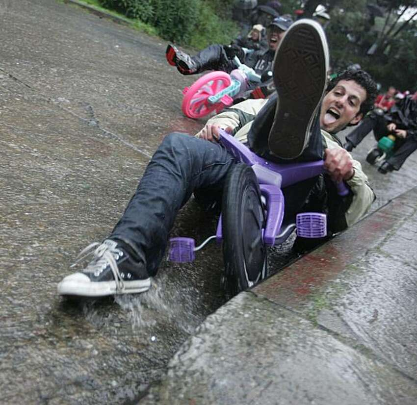A racer hits the curb as he zooms down Vermont Street in Potrero Hill during the tenth annual Bring Your Own Big Wheel Race on Sunday, April 4, 2010. A downpour dampened the crowds but not the enthusiasm of the hundreds of participants in the event.