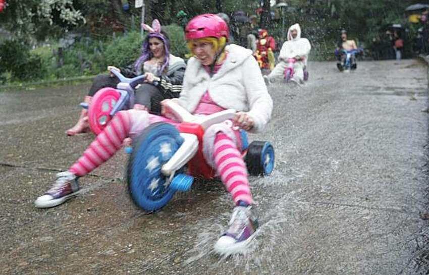 Racers zoom down Vermont Street in Potrero Hill during the tenth annual Bring Your Own Big Wheel Race on Sunday, April 4, 2010. A downpour dampened the crowds but not the enthusiasm of the hundreds of participants in the event.