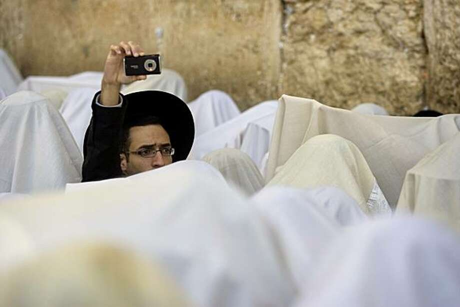 An ultra-orthodox Jewish man takes a photo as men of the Cohanim Priestly caste, covered in prayer shawls,  participate in a blessing during the Jewish holiday of Passover, at the Western Wall, Judaism's holiest site, in Jerusalem's Old City, Thursday, April 1, 2010. The Cohanim, believed to be descendants of priests who served God in the Jewish Temple before it was destroyed, perform a blessing ceremony of the Jewish people three times a year during the festivals of Passover, Shavuot and Sukkot. Photo: Sebastian Scheiner, AP